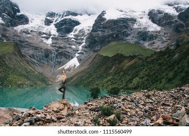Back view of young woman traveller doing yoga on rock of high hill enjoying scenery of amazing lake and beautiful mountains covered snows and clouds.Tourist in balance pose admiring trip in Salkantay