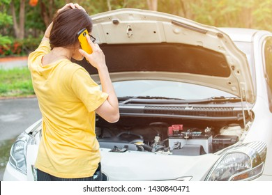 Back view of young woman trying to call someone to help her after her car breakdown on the road. Conceptual of car accident on the road