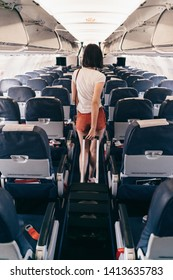 Back view of young woman walking the aisle on plane