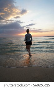 Back view of young woman wearing striped t-shirt and enjoying the sunset on the beach