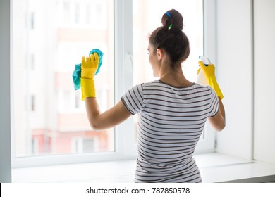 Back view of the young woman who washing the window with rag and window cleaner in the room