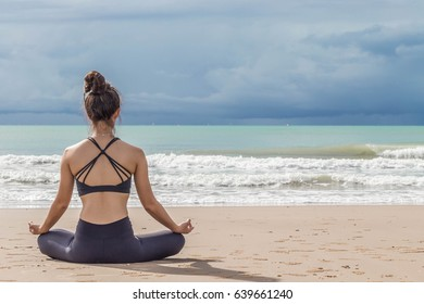 Back of view young woman yoga meditation lotus pose on the beach in thailand,Feeling so comfortable and relax in holiday,Healthy Concept