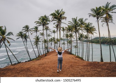 Back view of young yourist woman visiting Coconut tree hill in Mirissa, Sri Lanka. Coconut Tree Hill Mirissa is a unique cliff located at the end of a beach which is covered in palm trees.