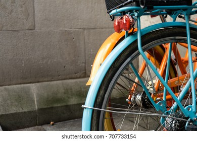 back wheel of orange and blue bycicle with concrete wall design retro hipster