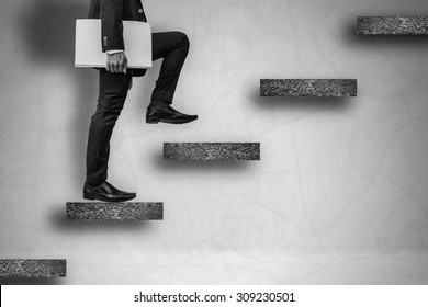 back and white businessman holding files climbing stairs on concrete wall