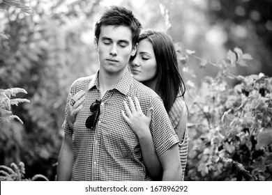 Back and white closeup portrait of young couple hugging with closed eyes at park