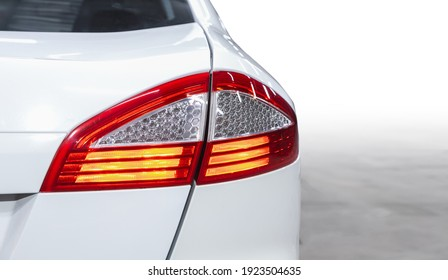 The back of a white expensive crossover car:  bumper, trunk lid, taillight on the back white background. Mock up for the advertising industry. New car concept