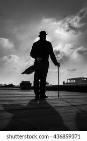 B;ack and white silhouette of a an elegant gentleman wearing a long a coattail with a cane and a  bowler hat
