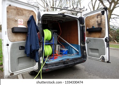 Back of white van in angle, with window cleaning equipment, water hoses, broom brush, cable, aluminium step ladders on roof rack. Space to add text on open doors & road side. Self employed job concept