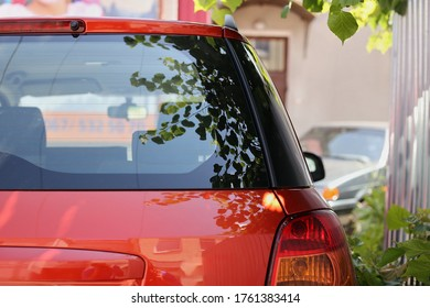 Back window of red car parked on the street in summer sunny day, rear view. Mock-up for sticker or decals
