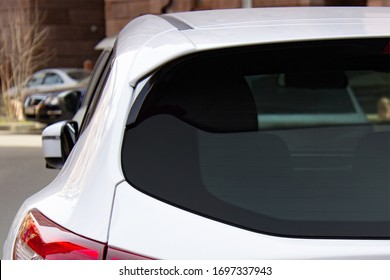 Back window of a white car parked on the street, rear view. Mock-up for sticker or decals