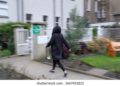Back of Woman in Black Parka Coat with Hood Up and Leggings Walking Briskly Quickly Away in Outdoors Urban City Park, Leaving Park Gate, Isolated, Blurred Background
