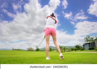 back of woman golf player concentrate in hit or chip the golf ball away to the destination green for winning in score rate