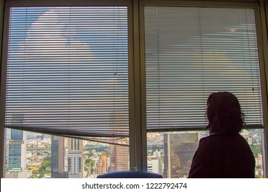 back of a woman looking at the view on tall building through a curtain, Louvers , shade, blind, shutters, jalousie window.