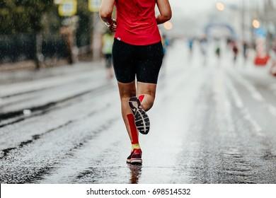 back woman running marathon in kinesiotape calf muscles