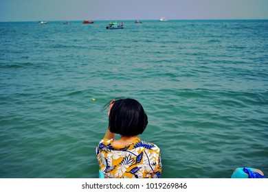 Back of woman in vintage shirt sit  in front of the ocean view, relax time in holidays, freedom, happy alone but not lonely, international women's day, single woman travel concept
