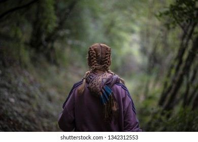 Back of a woman walking through the woods