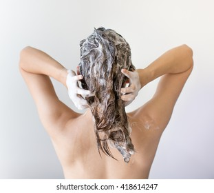 The back of a woman washing and shampooing her hair full of suds in front of a white background.
