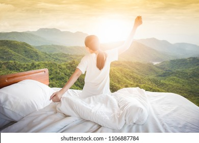 The back of the woman who woke up from bed in the morning on the nature background of the valley / fresh ideas health. Rest and holidays.