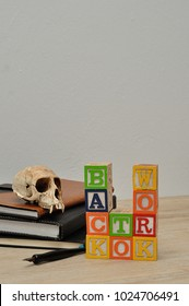 Back to work spelled in colorful blocks with a stack of books, a fountain pen and a monkey skull