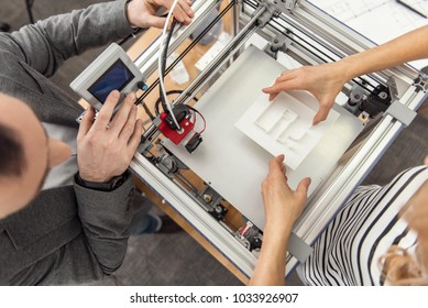 Back to work. The top view of young engineers inserting a model into the 3D printer and resuming the process of printing
