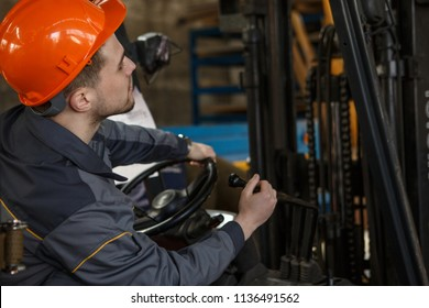 Back of worker wearing orange helmet and uniform  sitting and driving forklift on metal base. Professional loader looking carefully and transferring hardware. Concept of work.
