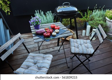 Back yard with  barbecue for family. Outdoor patio area with table and chairs.