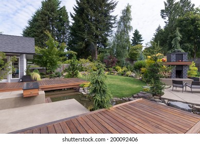 Back yard of a contemporary Pacific Northwest home featuring a deck a spanning creek-like water feature with a landscaped lawn and custom patio fireplace in the background.