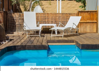 back yard exterior environment design with swimming pool and white lounge zone for rest in good summer weather time