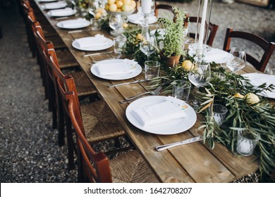 in the back yard of the old villa there is a long festive table, which is decorated with lemons and herbs, on the table are plates, glasses and candles. Wedding in Italy. Tuscany