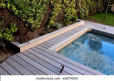 Piscina de jardín trasero con cubierta de madera, agua sucia dentro y pasto