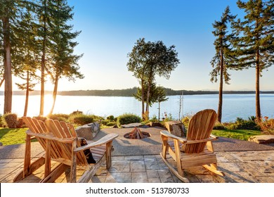 Back yard of waterfront house with adirondack chairs and fire pit.  Beautiful water view at sunset. Northwest, USA