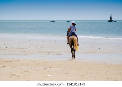 Back of young asian girl ridding horse on the beach with lighthouse in far background in the sea.