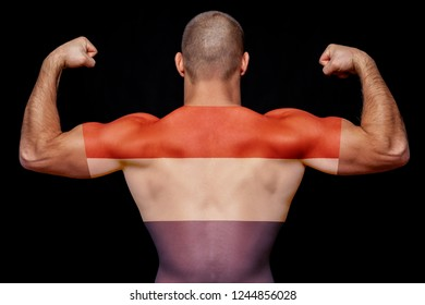 The back of a young athletic man wearing a t-shirt with the national flag of the Netherlands on a black isolated background. The concept of national pride and patriotism
