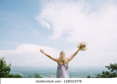 Back of young blonde woman standing in the maountains with a fantastic view