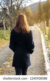 back of young brunette woman walking outdoors on a path