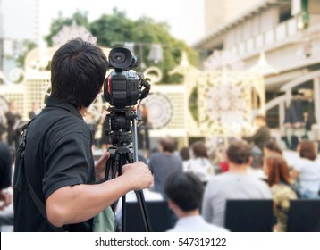 Back of young cameraman using a professional camcorder outdoor  filming music show or mini concert with blur background, Bangkok, Thailand