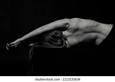 Back of young caucasian woman in dark studio
