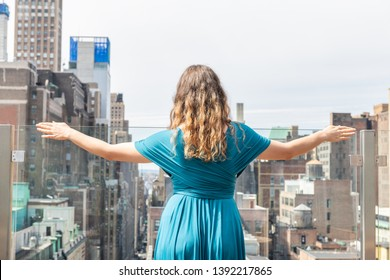 Back of young elegant woman standing back looking down on street cityscape skyline skyscrapers from rooftop in New York City NYC in green blue dress
