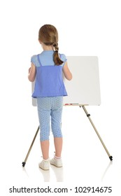 The back of a young elementary girl wrting on a white board.  The white board left blank for your message.  On a white background.