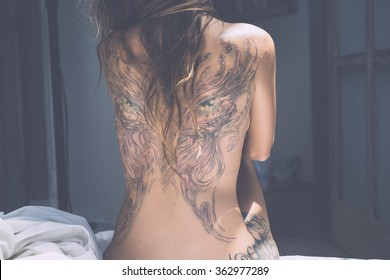the back of a young girl with a tattoo . Tanned beautiful girl with a tattoo on the entire back