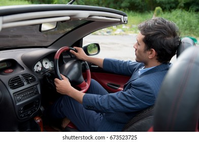 Back of an young handsome guy driving his convertible sport car, Man excited on road trip travel vacation. Male driver,Life style with beautiful cheerful lovers, Age 20-30 years.