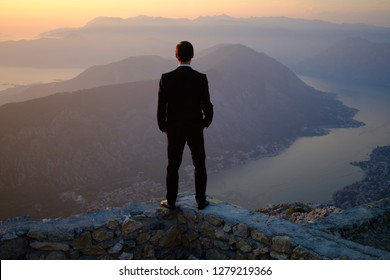 back of a young man in costume standing on a mountain at sunset. The groom or businessman looks from the top.