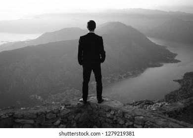 back of a young man in costume standing on a mountain at sunset. The groom or businessman looks from the top. Black and white photo