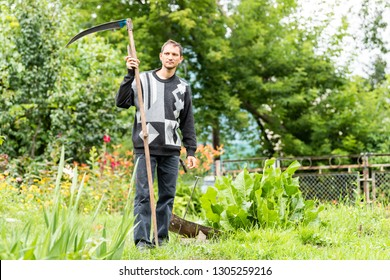 Back of young man farmer in garden standing with sickle scythe rake tool in green summer in Ukraine by well faucet