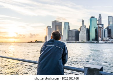 Back of young man outside outdoors in NYC New York City Brooklyn Bridge Park by east river, railing, looking at view of cityscape skyline sunset, statue liberty