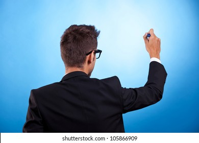 Back of young man in a suit writing or drawing something on blue background