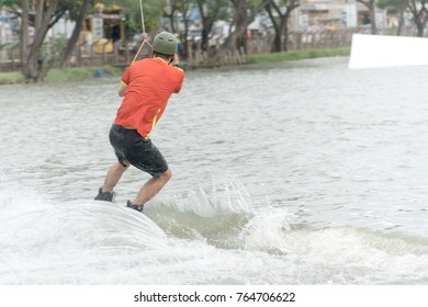 The back of the young man wake boarding on a lake with cable in Bangkok Thailand. Concept sport and leisure activities.