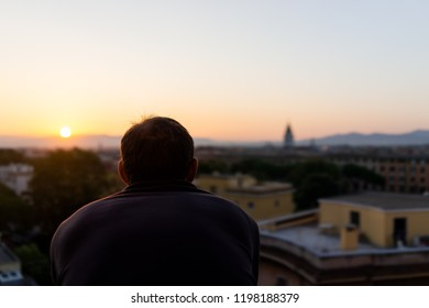 Back of young man watching sunset in Rome, Italy historic city with church tower, summer evening sunset night cityscape skyline, mountain aerial view of urban rooftops