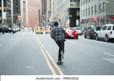 Back of young skateboarder cruise down the city street before sunset. Photographed in New York City in Feb 2016.